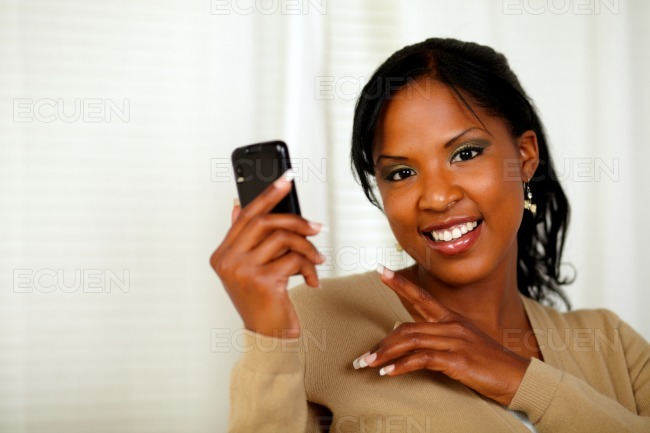 Charming woman reading a message on cellphone stock photo