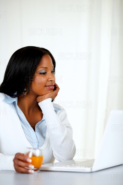 Charming woman reading on laptop screen stock photo
