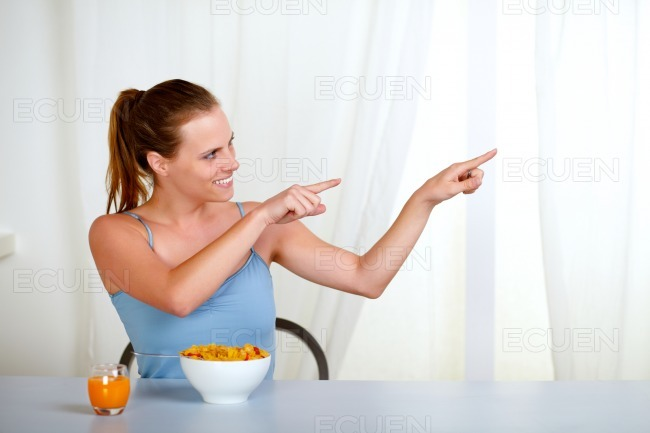 Charming youmg woman eating meal and pointing stock photo