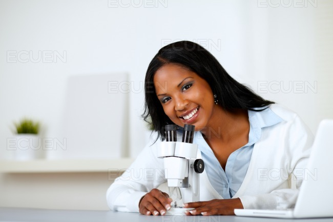 Charming young female using a microscope stock photo