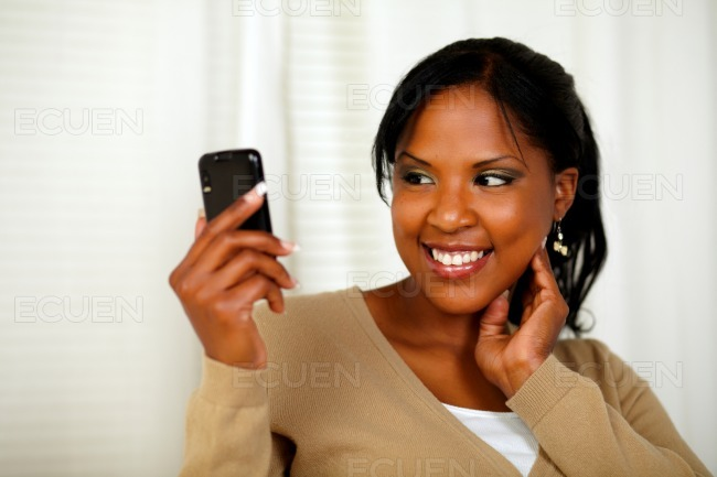 Charming young girl reading a message on cellphone stock photo