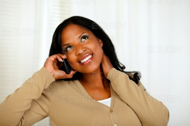 Charming young woman conversing on mobile phone stock photo