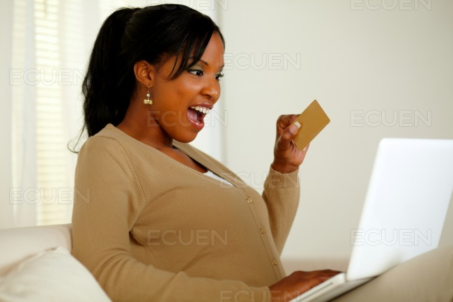Charming young woman holding a gold credit card stock photo