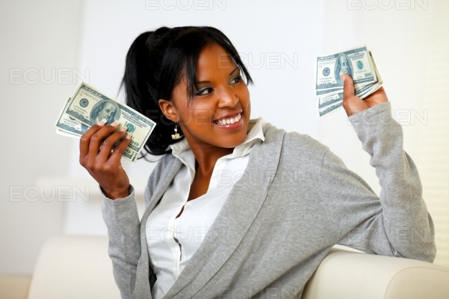 Charming young woman holding plenty of cash money stock photo