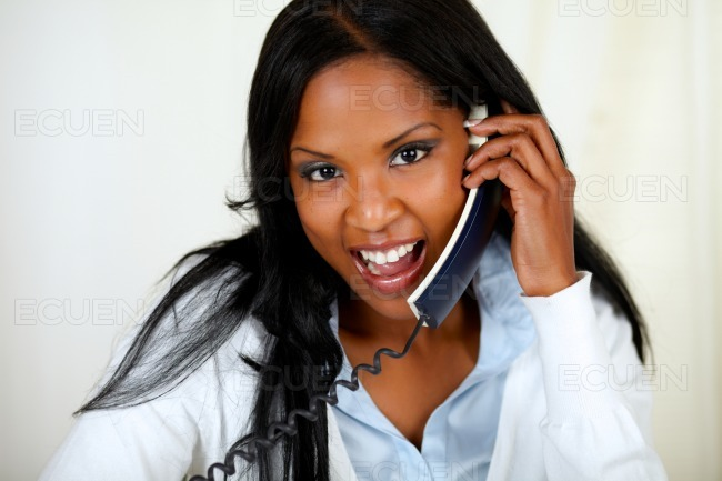 Charming young woman speaking on phone stock photo