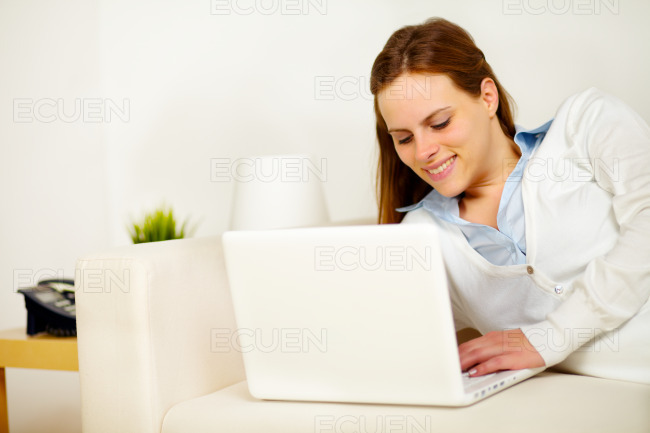 Cheerful lady lying on sofa with a laptop stock photo