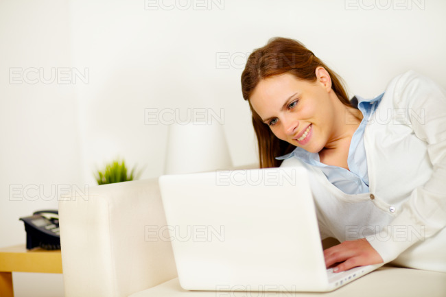 Cheerful woman lying on sofa with a laptop stock photo