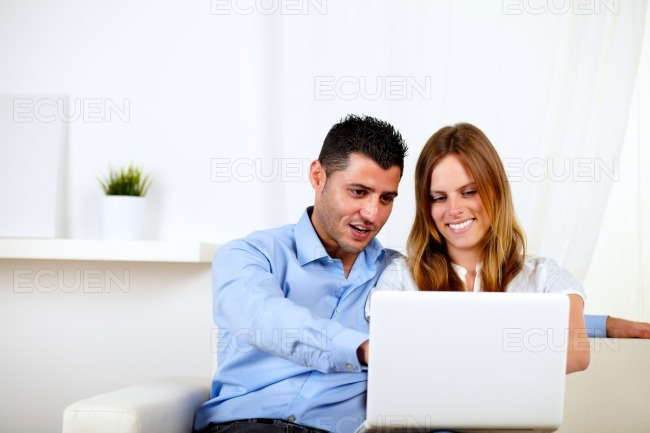 Couple in love using a computer at home stock photo