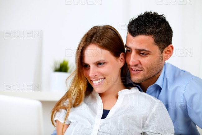 Couple in love using the laptop together at home stock photo
