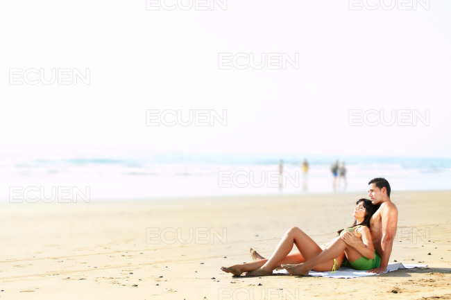 Couple lying on the beach stock photo
