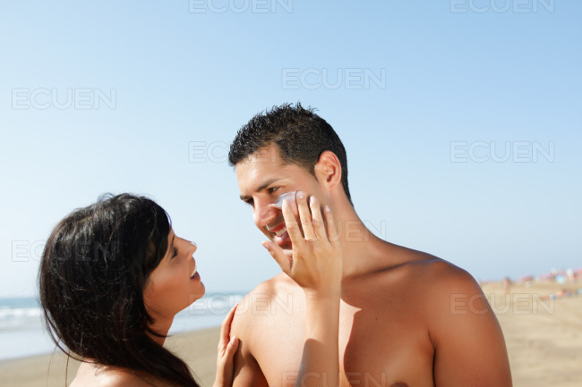 Couple on the beach putting on cream stock photo