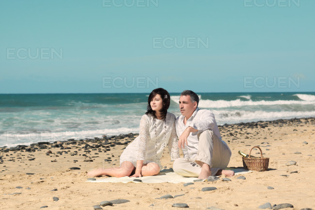 Couple sit down on the beach stock photo