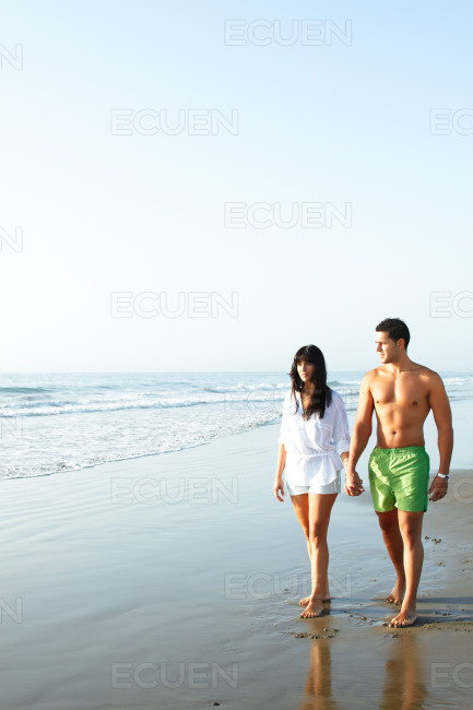 Couple walking along the seashore stock photo