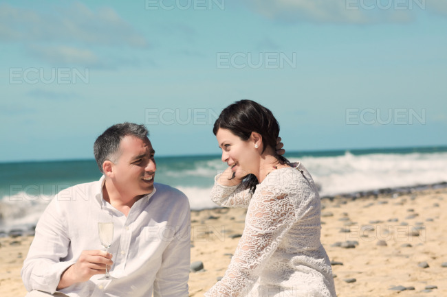 Couples talking and sitting on the beach stock photo