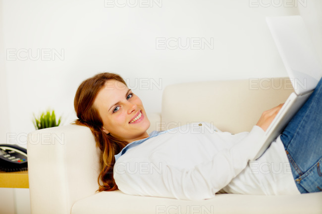 Cute woman smiling and lying on sofa stock photo