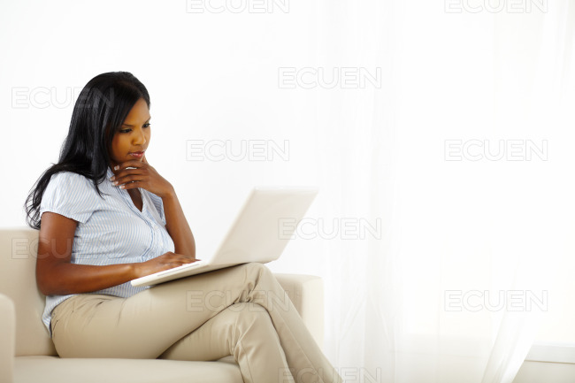 Cute woman with laptop on sofa stock photo