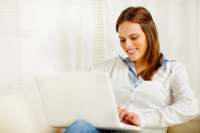 Cute young woman smiling and working on laptop stock photo