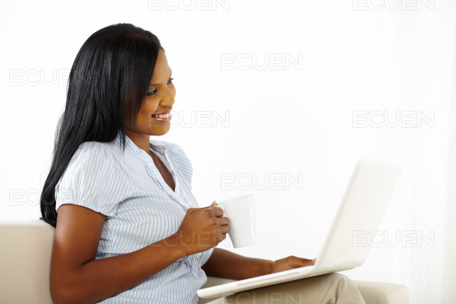 Cute young woman working on laptop at home stock photo