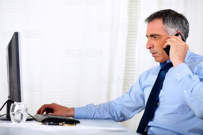 Elegant executive man conversing on cellphone stock photo