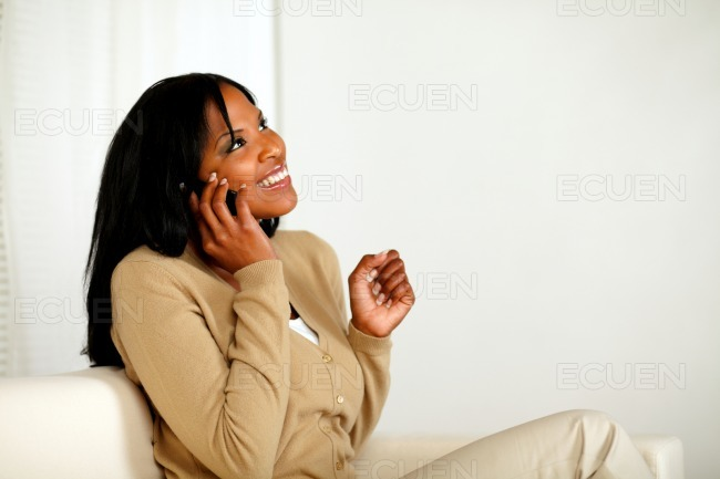 Excited afro-American woman conversing on phone stock photo