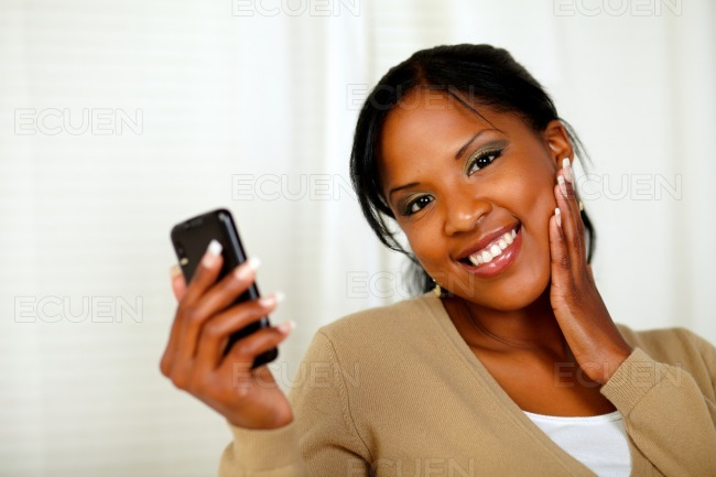 Fresh woman holding a mobile and looking to you stock photo