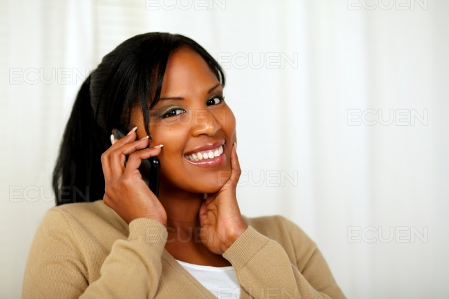 Fresh woman looking to you and talking on mobile stock photo