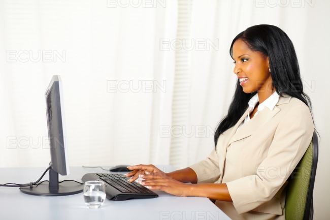 Friendly businesswoman working on computer stock photo