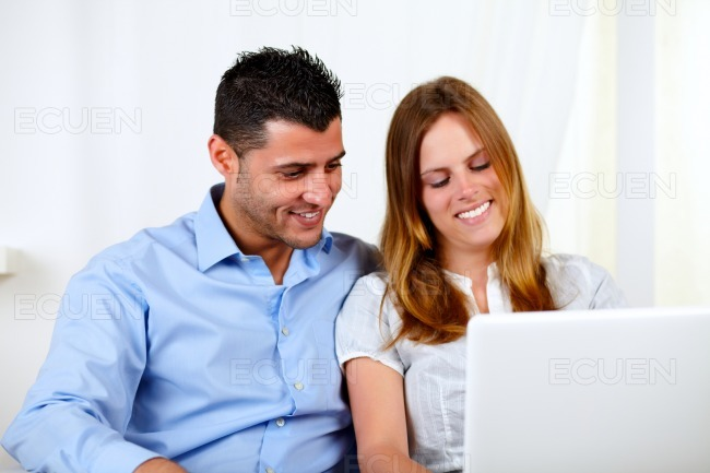 Friendly couple using a laptop stock photo