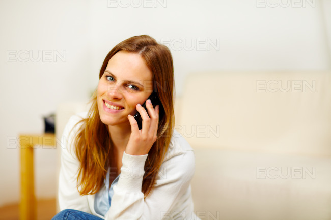 Friendly girl speaking on the phone at home stock photo