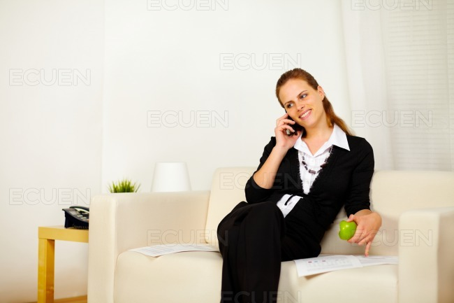 Friendly young business woman working on sofa stock photo