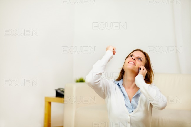 Girl on mobile phone celebrating a victory stock photo