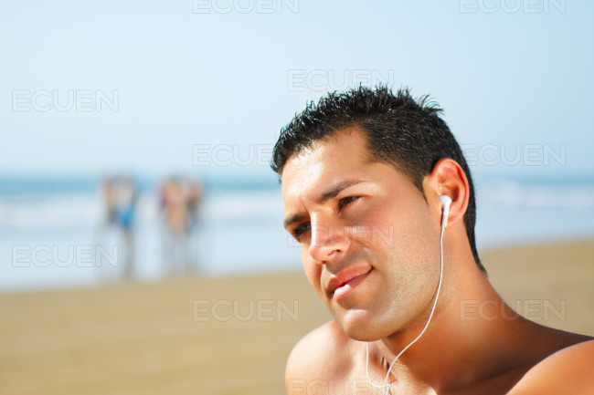 Guy on the beach listening to music stock photo