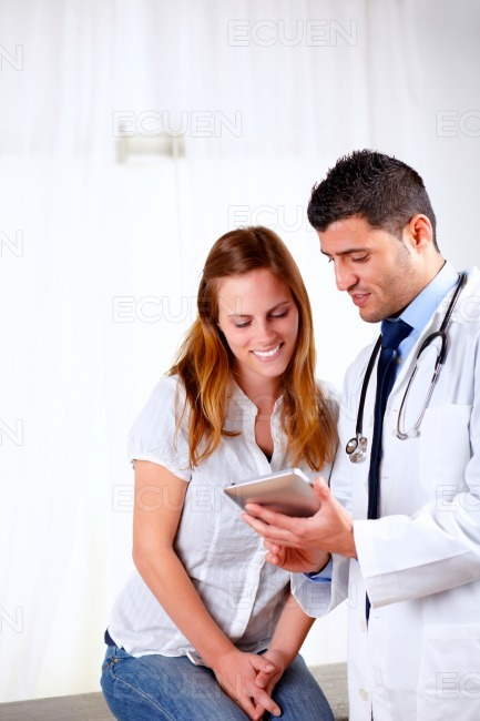 Handsome doctor and a patient looking to tablet PC stock photo