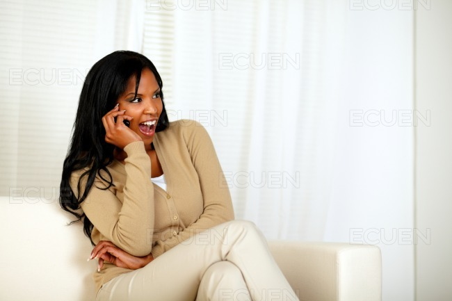 Happy and surprised woman talking on cellphone stock photo