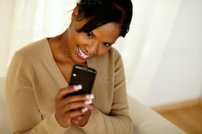 Happy black female sending a message by cellphone stock photo