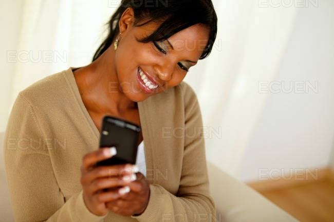 Happy black woman sending a message by cellphone stock photo