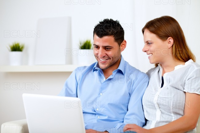 Happy young couple working on laptop stock photo
