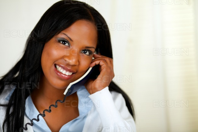 Happy young female speaking on phone stock photo