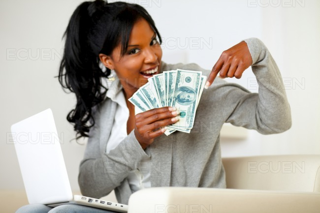 Happy young woman pointing plenty of cash money stock photo