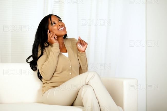 Happy young woman sitting at home on sofa stock photo