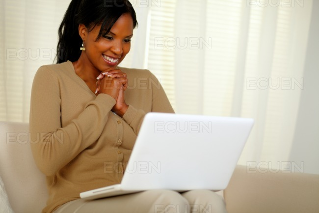 Happy young woman smiling and looking to laptop stock photo