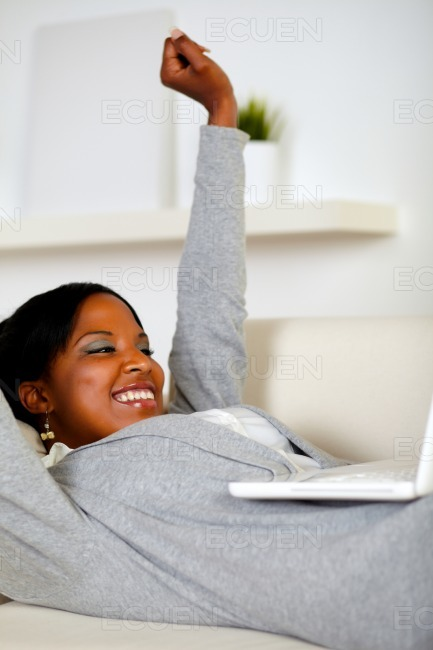 Happy young woman working on laptop stock photo