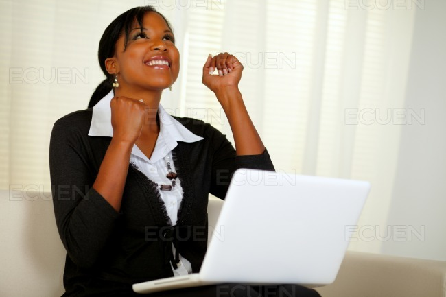 Happy young woman working on laptop and looking up stock photo