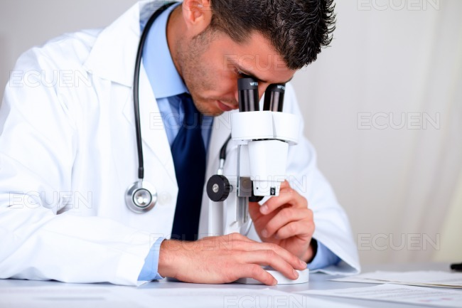 Hispanic professional doctor with a microscope stock photo