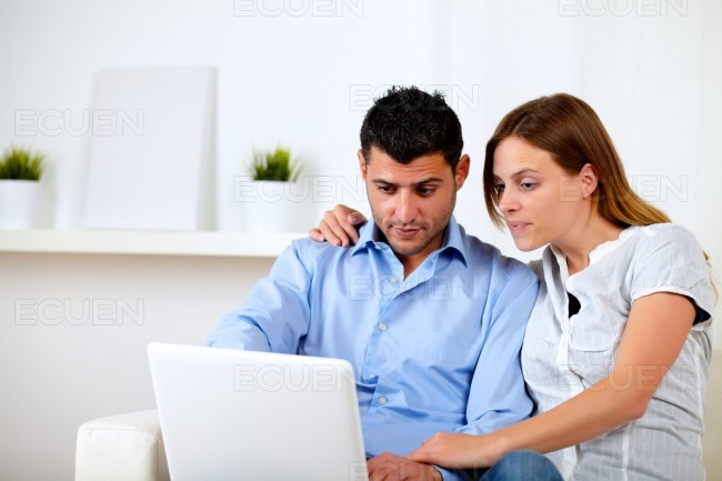Interested couple browsing on laptop stock photo