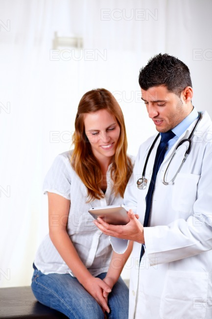Latin doctor and a female looking to tablet PC stock photo