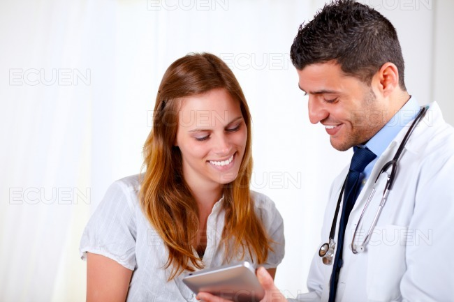 Latin doctor and a patient looking to tablet PC stock photo