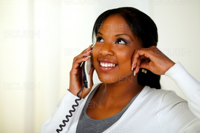 Lovely black woman smiling and conversing on phone stock photo