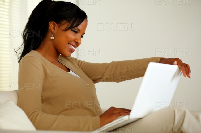 Lovely black woman smiling and looking to laptop stock photo