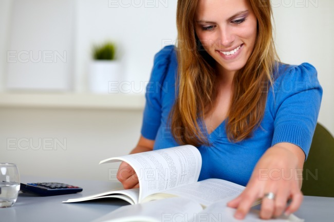 Lovely blonde girl smiling and reading stock photo
